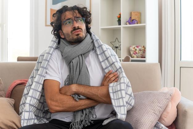 Unzufriedener junger kranker kaukasischer mann in optischer brille, eingewickelt in plaid mit schal um den hals, sitzt auf der couch mit verschränkten armen und blickt auf die seite des wohnzimmers