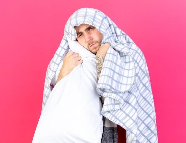 Unzufriedener junger kranker mann, der in plaid gewickelt hält, hält kissen lokalisiert auf rosa wand