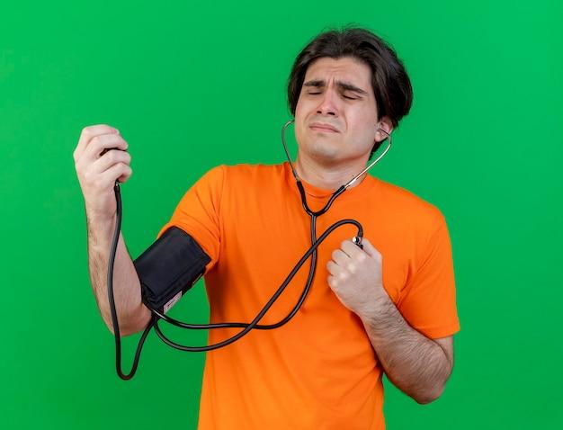 Unzufriedener junger kranker mann, der seinen eigenen druck mit dem auf grün isolierten blutdruckmessgerät misst