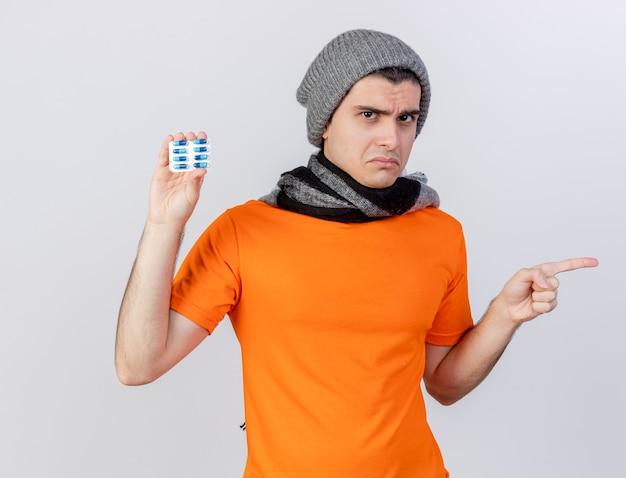 Unzufriedener junger kranker mann, der wintermütze mit schal hält, der pillen und punkte seitlich lokalisiert auf weiß hält
