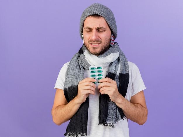 Unzufriedener junger kranker mann, der wintermütze mit schal trägt, der pillen unter hut setzt und pillen hält, die auf purpur isoliert werden