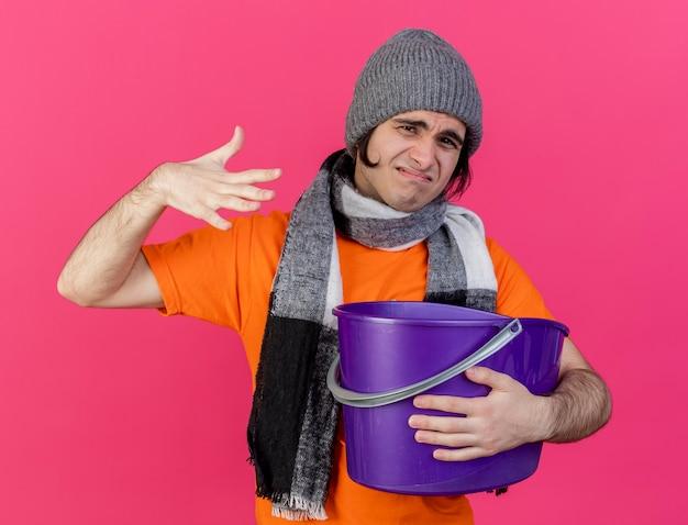 Unzufriedener junger kranker mann, der wintermütze mit schal trägt, der übelkeit hält, der plastikeimer lokalisiert auf rosa hält