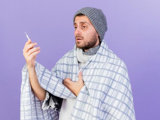 Unzufriedener junger kranker mann, der wintermütze mit schal wickelt, der im karierten halten und im betrachten des thermometers lokalisiert auf purpurrotem hintergrund eingewickelt ist