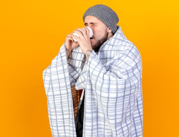 Unzufriedener junger kranker mann, der wintermütze und schal trägt, die in die tasse tee der karierten getränke eingewickelt werden, lokalisiert auf orange wand