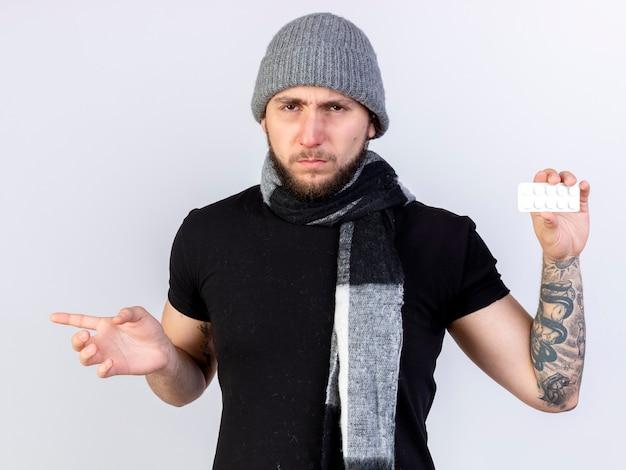 Unzufriedener junger kranker mann, der wintermütze und schal trägt, hält packung der medizinischen tabletten und punkte an der seite lokalisiert auf weißer wand