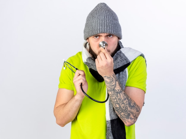 Unzufriedener junger kranker mann, der wintermütze und schal trägt, hält stethoskop und setzt nase auf weiße wand isoliert