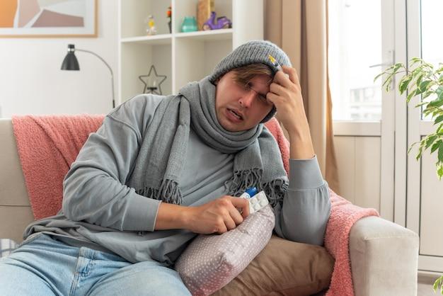 Unzufriedener junger kranker mann mit schal um den hals, der eine wintermütze mit spritze und medikamentenblisterpackung und thermometer auf der couch im wohnzimmer trägt