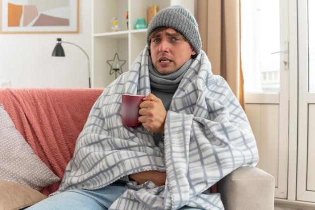 Unzufriedener junger kranker mann mit schal um den hals, der eine wintermütze trägt, die in eine karierte tasse eingewickelt ist, die auf der couch im wohnzimmer sitzt