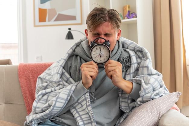 Unzufriedener junger kranker mann mit schal um den hals, der eine wintermütze trägt, die in plaid gehüllt ist und einen wecker auf der couch im wohnzimmer hält