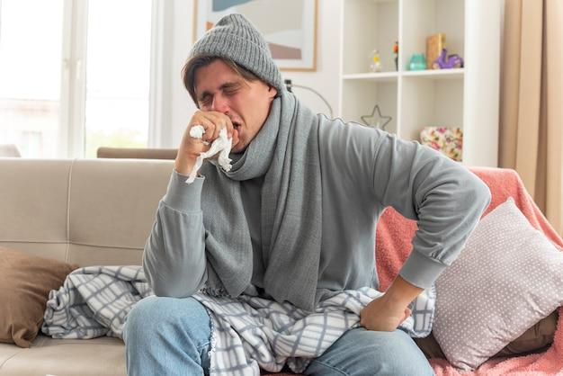 Unzufriedener junger kranker mann mit schal um den hals, der eine wintermütze trägt, niest die hand nah am gesicht auf der couch im wohnzimmer sitzend