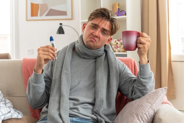 Unzufriedener junger kranker mann mit schal um den hals, der thermometer und tasse auf der couch im wohnzimmer hält