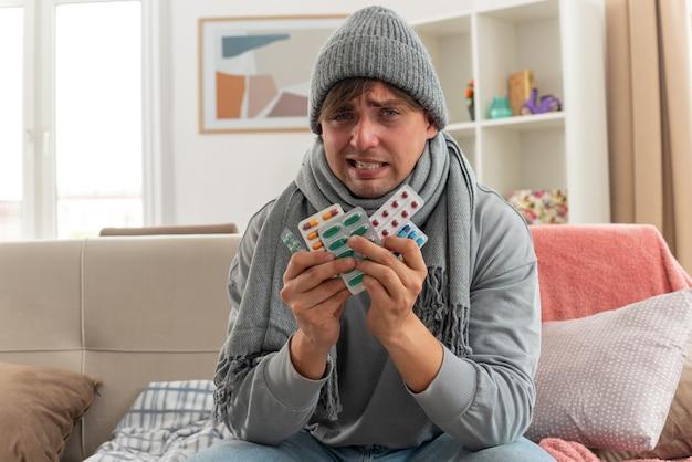 Unzufriedener junger kranker mann mit schal um den hals mit wintermütze, der medizinblisterpackungen auf der couch im wohnzimmer hält