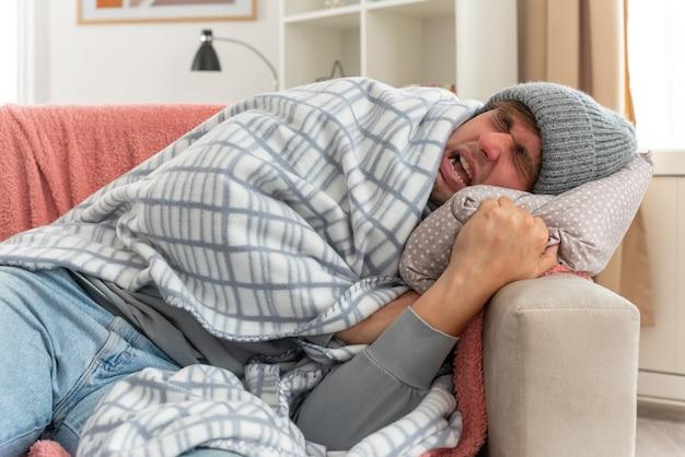 Unzufriedener junger kranker slawischer mann mit schal um den hals, der eine wintermütze trägt, die in plaid gehüllt auf der couch im wohnzimmer liegt