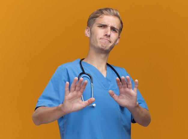 Unzufriedener junger männlicher arzt, der arztuniform mit stethoskop hält, das hände an kamera lokalisiert auf orange wand heraushält