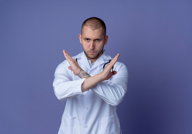 Unzufriedener junger männlicher arzt, der medizinische robe und stethoskop um seinen hals trägt und keine geste an der kamera tut, die auf lila hintergrund mit kopienraum isoliert wird