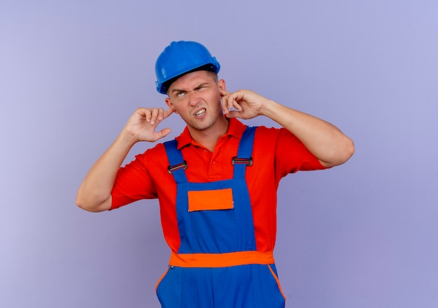 Unzufriedener junger männlicher baumeister, der uniform und schutzhelm trägt, schloss ohren auf purpur