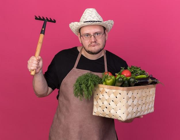 Unzufriedener junger männlicher gärtner, der gartenhut hält, der gemüsekorb erhöht, der rechen auf rosa wand lokalisiert