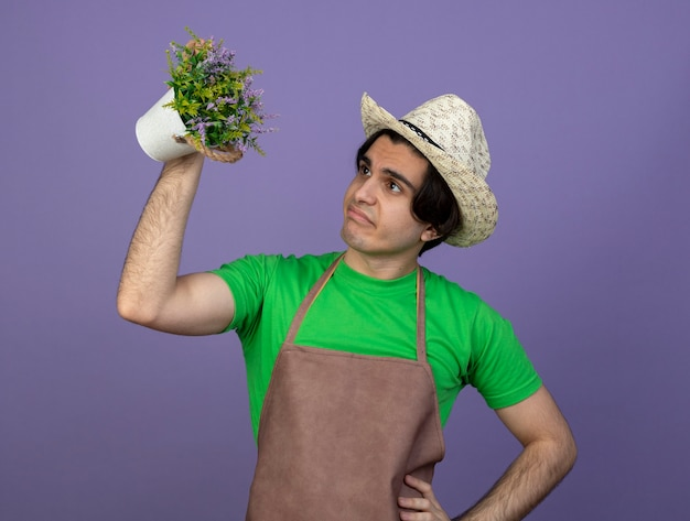 Unzufriedener junger männlicher gärtner in der uniform, die gartenhut trägt, der blume im blumentopf anhebt und hand auf hüfte setzt, die auf purpur lokalisiert