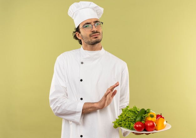 Unzufriedener junger männlicher koch, der kochuniform und gläser trägt, die gemüse auf teller halten und stoppgeste zeigen