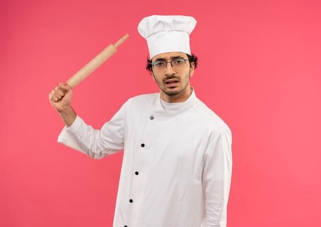 Unzufriedener junger männlicher koch, der kochuniform und gläser trägt, die nudelholz um schulter halten