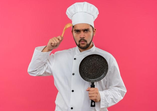 Unzufriedener junger männlicher koch in der kochuniform, die bratpfanne und berührenden kopf mit löffel lokalisiert auf rosa raum hält