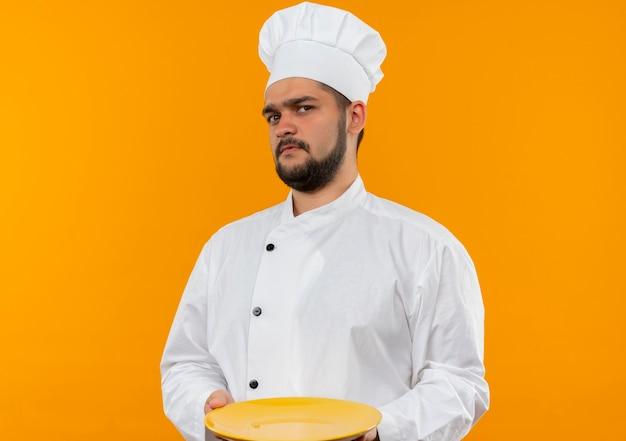 Unzufriedener junger männlicher koch in der kochuniform, die leeren teller lokalisiert auf orange raum hält
