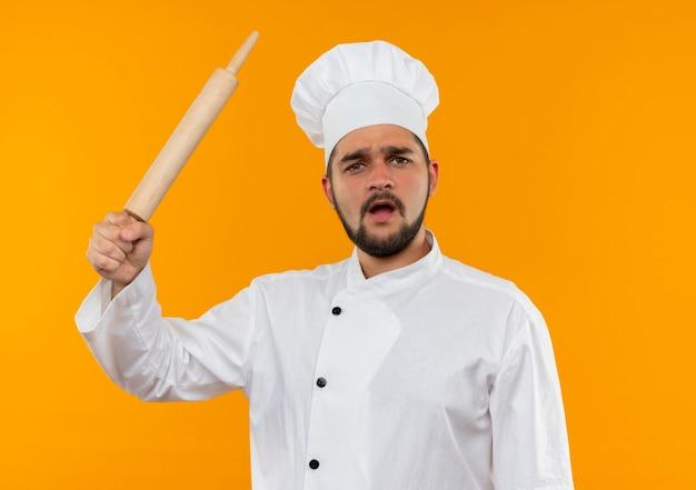 Unzufriedener junger männlicher koch in der kochuniform, die nudelholz anhebt, lokalisiert auf orange raum