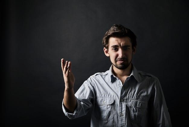 Unzufriedener junger mann, der mit einer hand auf schwarzem hintergrund gestikuliert
