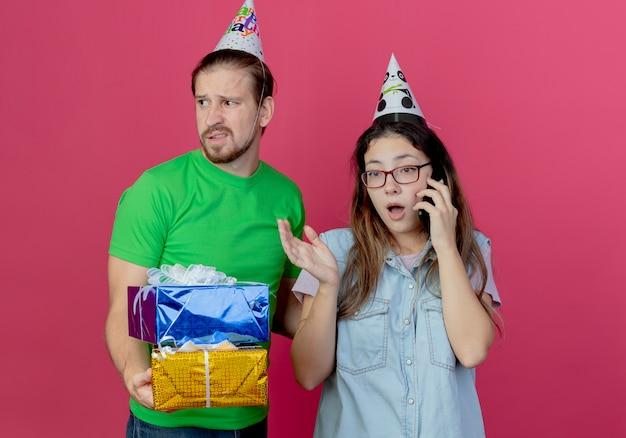 Unzufriedener junger mann, der partyhut trägt, hält geschenkboxen und schaut zur seite stehend mit überraschtem jungem mädchen, das partyhut trägt und am telefon lokalisiert auf rosa wand spricht