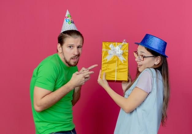 Unzufriedener junger mann, der partyhut trägt, zeigt auf geschenkbox, die durch junges mädchen hält, das blauen partyhut lokalisiert auf rosa wand hält