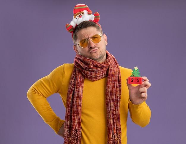Unzufriedener junger mann im gelben rollkragenpullover mit warmem schal und brille, die lustigen rand mit weihnachtsmann auf kopf tragen spielzeugspielwürfel mit nummer fünfundzwanzig stehen über lila wand