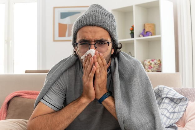 Unzufriedener junger mann in optischer brille, eingehüllt in plaid mit wintermütze, wischt sich die nase mit einem taschentuch ab und schaut nach vorne auf der couch im wohnzimmer sitzen