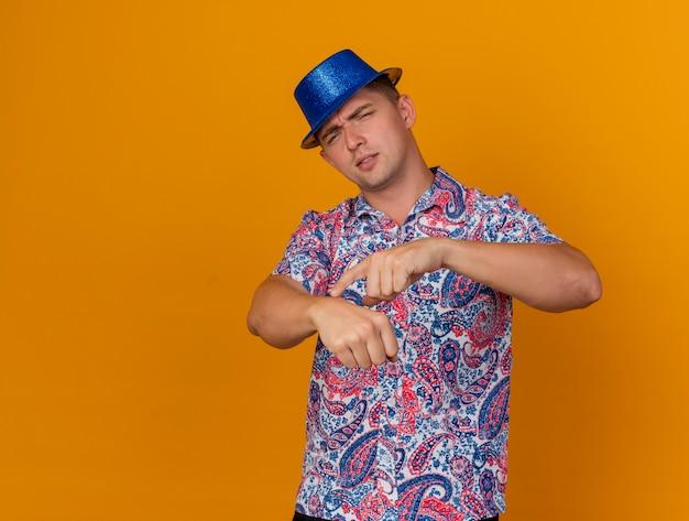 Unzufriedener junger party-typ, der blauen hut trägt, der armbanduhrgeste zeigt, die auf orange lokalisiert wird