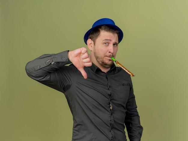 Unzufriedener junger party-typ, der ein schwarzes hemd und einen blauen hut trägt, der party-gebläse bläst und daumen nach unten lokalisiert auf olivgrün zeigt