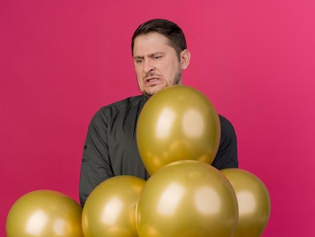 Unzufriedener junger party-typ, der schwarzes hemd trägt, das hinter den auf rosa isolierten luftballons steht