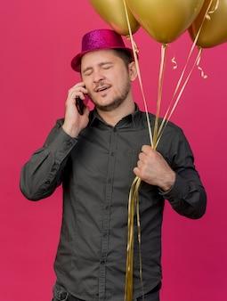 Unzufriedener junger party-typ mit geschlossenen augen, der rosa hut hält, der luftballons hält, spricht am telefon isoliert auf rosa