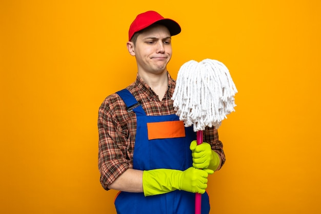 Unzufriedener junger putzmann mit uniform und mütze mit handschuhen, die mop halten und betrachten