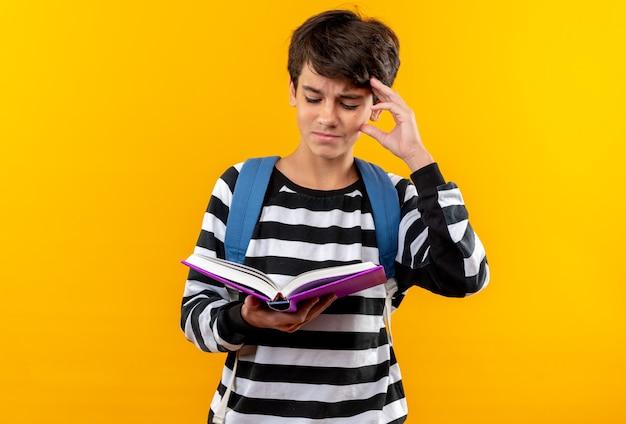 Unzufriedener junger schuljunge mit rucksack, der ein buch hält und liest, das hand auf den kopf legt