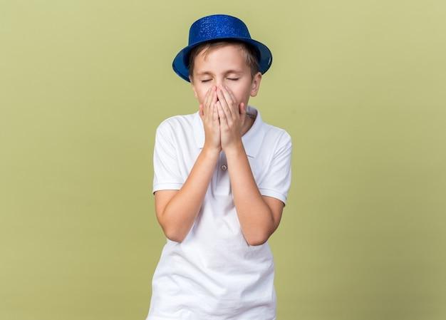 Unzufriedener junger slawischer junge mit blauem partyhut niest den mund mit den händen bedeckt, isoliert auf olivgrüner wand mit kopierraum