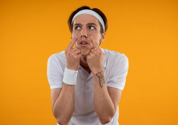 Unzufriedener junger sportlicher kerl, der stirnband und armband trägt und augenlider herunterzieht, die auf orange wand lokalisiert werden