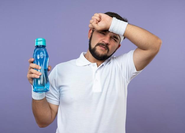 Unzufriedener junger sportlicher mann, der stirnband und armband hält wasserflasche hält und hand auf stirn legt