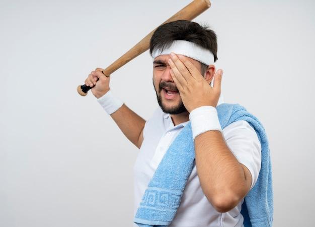 Unzufriedener junger sportlicher mann, der stirnband und armband mit handtuch auf der schulter trägt, die baseballschläger bedeckte gesicht mit hand lokalisiert auf weißer wand mit kopienraum