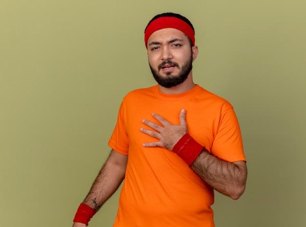 Unzufriedener junger sportlicher mann, der stirnband und armband trägt, die hand auf brust lokalisiert auf olivgrünem hintergrund setzen