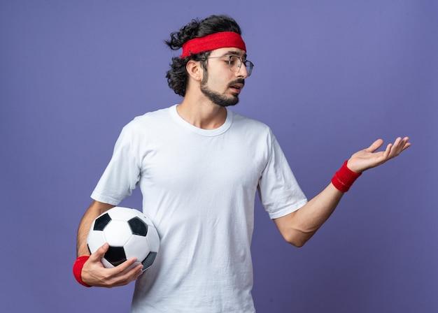 Unzufriedener junger sportlicher mann mit stirnband mit armband, das den ball hält, der die hand an der seite ausstreckt