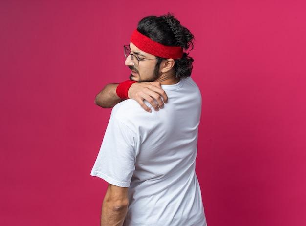 Unzufriedener junger sportlicher mann mit stirnband mit armband packte schmerzende schulter