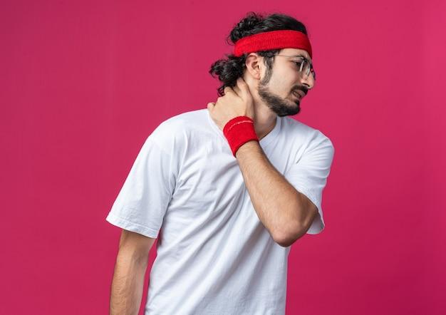 Unzufriedener junger sportlicher mann mit stirnband mit armband packte schmerzenden nacken