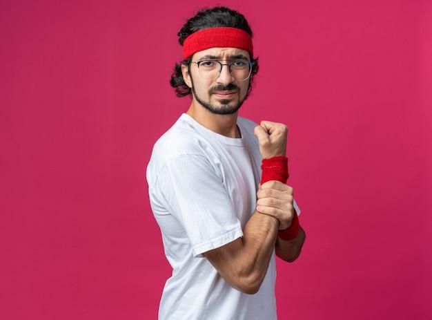 Unzufriedener junger sportlicher mann mit stirnband mit armband packte schmerzendes handgelenk