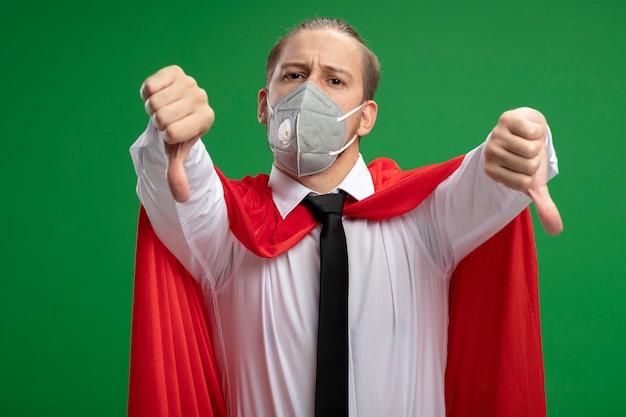 Unzufriedener junger superheld, der medizinische maske und krawatte trägt, die daumen unten lokalisiert auf grünem hintergrund zeigt