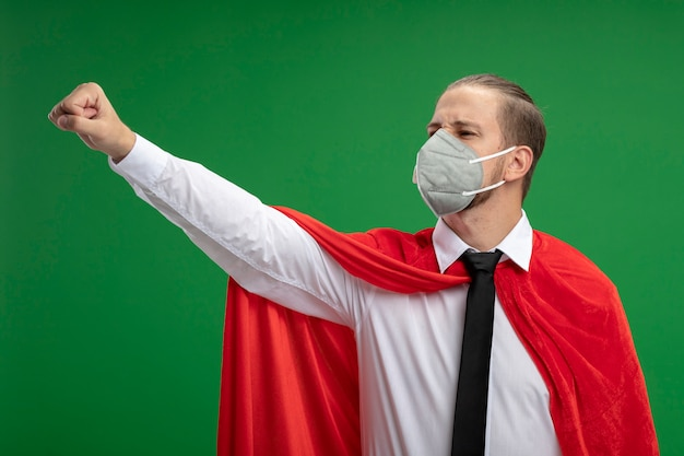Unzufriedener junger superhelden-typ, der medizinische maske und krawattenerhöhungsfaust lokalisiert auf grünem hintergrund trägt
