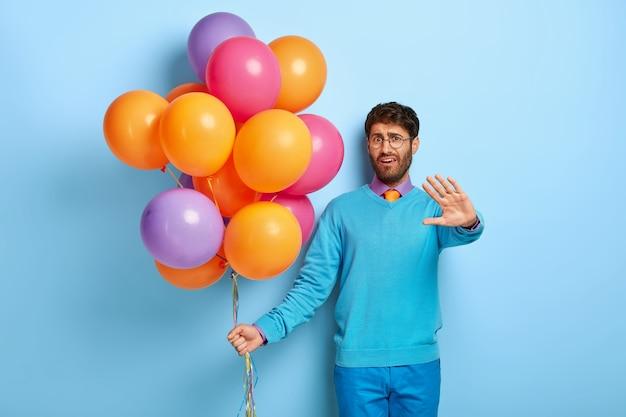 Unzufriedener kerl mit luftballons, die im blauen pullover aufwerfen